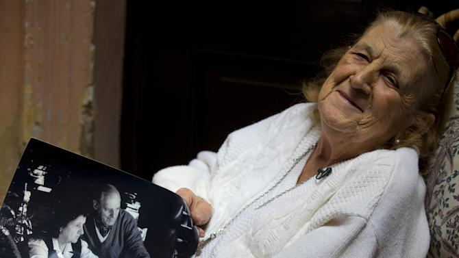 """In this April 12, 2013 photo, Clelia Luro shows a picture of herself with her late husband, Jeronimo Podesta, a former bishop of Avellaneda, at her home in Buenos Aires, Argentina. Luro, whose romance with the former bishop and eventual marriage became a major scandal in the 1960s, is such a close friend with Pope Francis that he called her every Sunday when he was Argentina's leading cardinal. She's convinced that Pope Francis will eventually lead the global church to end mandatory priestly celibacy, a requirement she says """"the world no longer understands."""" (AP Photo/Natacha Pisarenko)"""