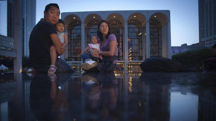 A family sits on the granite bench that surrounds a fountain in front of the Metropolitan Opera House at Lincoln Center in New York