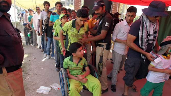 A Pakistani police officer frisks cricket fans arriving to Gaddafi Stadium for a one-day international match between Pakistan and Zimbabwe in Lahore, Pakistan, Tuesday, May 26, 2015. Pakistan captain Azhar Ali won the toss and elected to bat in the first one-day international against Zimbabwe.  (AP Photo/K.M. Chaudary)