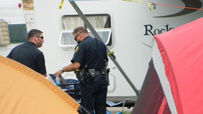 Clarksville Police survey the trailer where five people were found dead Sunday, Sept. 18, 2011 in Clarksville, Tenn., at the Clarksville Speedway. The deaths brought an abrupt halt to the celebration of the state's largest toy run for needy children, which was hosted Saturday at the speedway by Bikers Who Care. (AP Photo/The Leaf-Chronicle, Luke Thomspson)