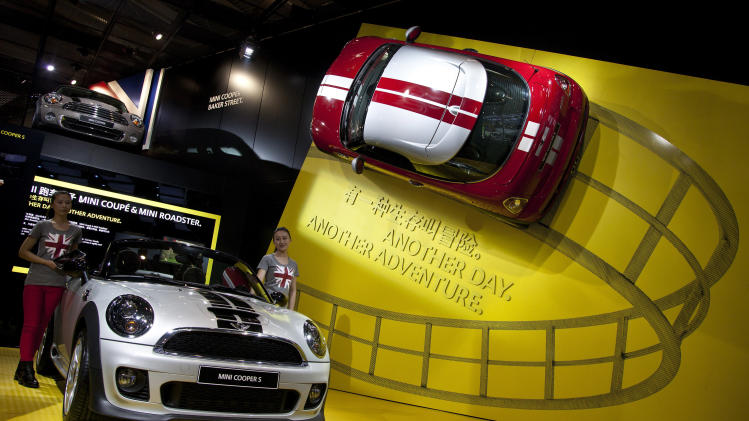 Models stand next to the Mini Cooper S on display at the Beijing International Automotive Exhibition in Beijing, China Monday, April 23, 2012. (AP Photo/Andy Wong)