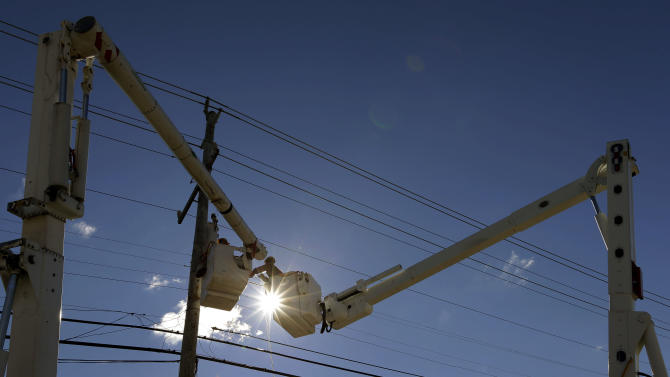 FILE - In this Saturday, Nov. 3, 2012, file photo, a utility crew works to restore power on Long Beach Island, N.J., after communities on the island sustained damage from Superstorm Sandy.  With 1.9 million residents still without power, 67,000 utility workers are trying to restore power in the Northeast. But besides cleaning parts, testing wires and cutting trees, the storm surge added another dimension to the work by attacking the utilities' internal equipment. (AP Photo/Patrick Semansky, File)