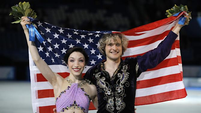 Meryl Davis and Charlie White of the United States pose for photographers after placing first in the ice dance free dance figure skating finals at the Iceberg Skating Palace during the 2014 Winter Olympics, Monday, Feb. 17, 2014, in Sochi, Russia. (AP Photo/Vadim Ghirda)