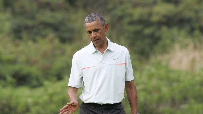 U.S. President Barack Obama gestures after missing his putt as Malaysia's PM Najib Razak play on the 18th green at the Clipper Golf course in Kaneohe