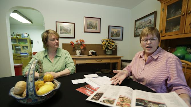"""Kimberly Bliss, left, and her wife Kim Ridgway, right, look at recepies for marijuana """"edibles"""" as they sit at their dining room table, Wednesday, Feb. 27, 2013 at their home in Lacey, Wash. The couple got married on Dec. 9, 2012, thanks to the state's new gay marriage law, and now they are trying to take advantage of another measure voters approved in November by planning to open a state-licensed marijuana store. (AP Photo/Ted S. Warren)"""