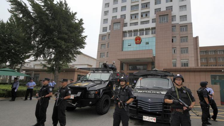 Police from the SWAT team stand guard outside a court during the trial of five cult members charged with murder in Zhaoyuan
