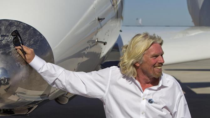 British billionaire Sir Richard Branson stands along side the spacecraft White Knight Two after a test flight outside the new Spaceport America hangar Monday, Oct. 17, 2011 in Upham, NM. Branson dedicated the newly completed terminal Monday where his Virgin Galactic is slated to begin his commercial space tourism venture from the remote patch of desert in Sierra County. (AP Photo/Matt York)