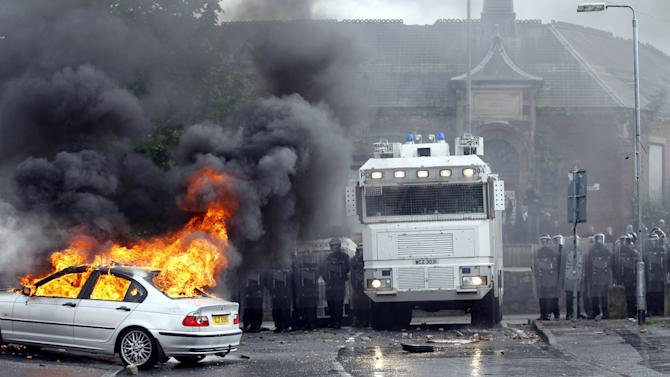 A car burns after Nationalist rioters clashed with Police Service of Ireland in the Ardoyne area of North Belfast, Northen Ireland, Thursday, July 12, 2012.  Trouble broke out after an Orange Order march passed the area.  The Twelfth of July is the busiest day of the marching season in Northern Ireland with thousands of Orangemen and women, accompanied by marching bands, taking part in hundreds of parades. The Orange Order holds its main Belfast event, which commemorates King William III's 1690 Battle of the Boyne victory over Catholic King James II. (AP Photo/Peter Morrison)