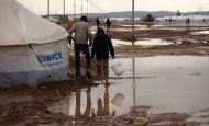 Syrian refugees walk on water and mud, at Zaatari Syrian refugee camp, near the Syrian border in Mafraq, Jordan, Tuesday, Jan. 8, 2013. Syrian refugees in a Jordanian camp attacked aid workers with sticks and stones on Tuesday, frustrated after cold, howling winds swept away their tents and torrential rains flooded muddy streets overnight. Police said seven aid workers were injured. (AP Photo/Mohammad Hannon)