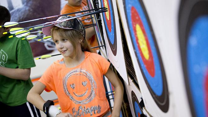 "In this April 13, 2012 photo, Christa Mattessich of Oakland, N.J., 7, retrieves her arrows after a round in the youth archery league at Targeteers Archery in Saddle Brook, N.J.  In schools and backyards, for their birthdays and out with their dads, kids are gaga for archery a month after the release of ""The Hunger Games."" Archery ranges around the country have enjoyed a steady uptick among kids of both sexes in the movie's lead-up, though 16-year-old heroine Katniss Everdeen, the archery ace seems to resonate with girls more than boys. (AP Photo/Charles Sykes)"