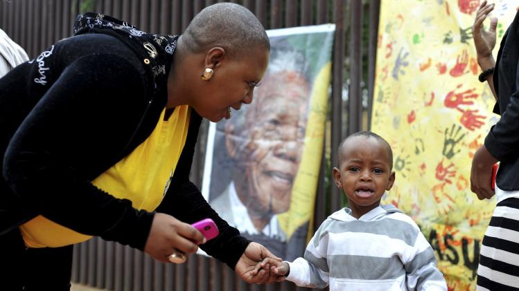 Mother consoles her crying son during a gathering for people mourning the death of former South African President Mandela on Vilakazi Street in Soweto