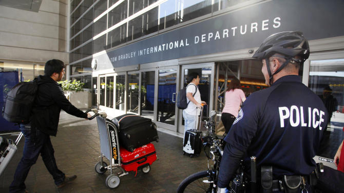 A Los Angeles Police officer patrols outside the departure area at Los Angeles International Airport on Wednesday, Oct. 16, 2013. Police at Los Angeles International Airport are continuing their stepped-up patrols the day after the arrest of a baggage handler in connection with a pair of small explosions. (AP Photo/Nick Ut)