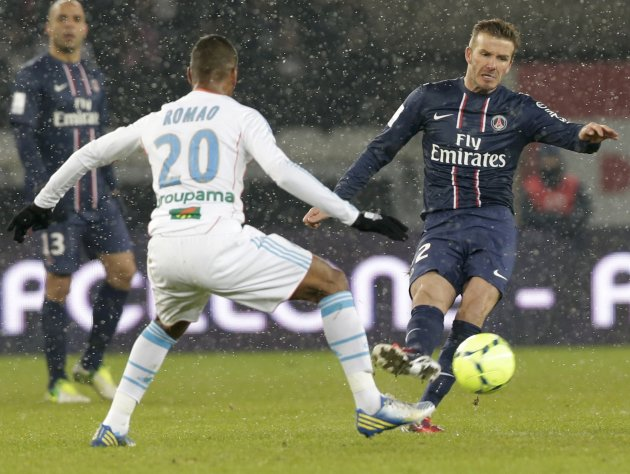 Paris Saint-Germain's Beckham challenges Olympic Marseille's Romao during their French Ligue 1 soccer match at Parc des Princes stadium in Paris