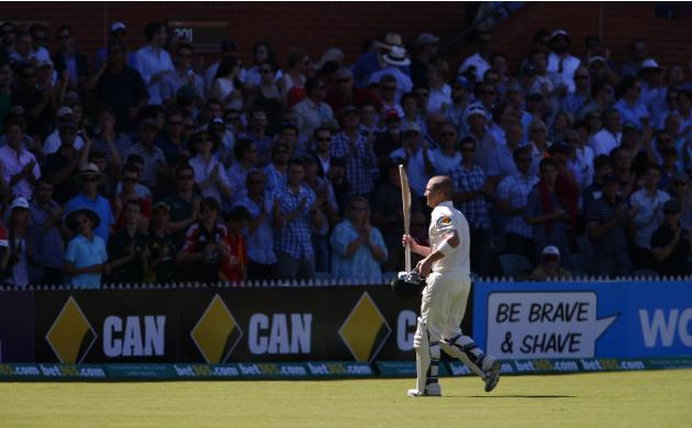 Australia's Brad Haddin raises his bat at the crowd as he walks off the field after his dismissal during the second day's play in the second Ashes cricket test against England at the Adelaide