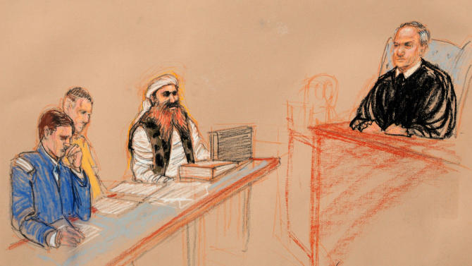 ** CLARIFIES THAT MAJ. POTEET IS NOT A RESERVIST BUT AN ACTIVE DUTY OFFICER ** In this photo of a sketch by courtroom artist Janet Hamlin and reviewed by the U.S. Department of Defense, Khalid Sheikh Mohammed, third from left, wearing a camouflage vest and sitting at a defense table with his legal team, U.S. Army Capt. Jason Wright, left, and U.S. Marine Corps Major Derek Poteet, addresses judge U.S. Army Col. James Pohl during the third day of the Military Commissions pretrial hearing against the five Guantanamo prisoners accused of the Sept. 11 terrorist attacks at the Guantanamo Bay U.S. Naval Base in Cuba, Wednesday, Oct. 17, 2012. Khalid Sheikh Mohammed, who has told authorities he was the mastermind of the Sept. 11 hijacking plot, wore the woodland-style camouflage vest for the first time Wednesday, a clothing choice previously denied because of fears it might disrupt the court. (AP Photo/Janet Hamlin, Pool)