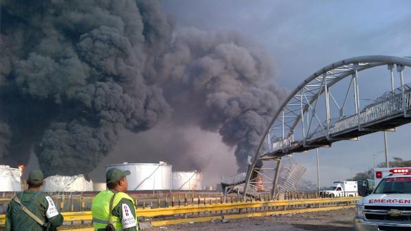 Large plumes of smoke rise from the Amuay refinery as national guardsmen watch near Punto Fijo, Venezuela, Saturday, Aug. 25, 2012. A huge explosion rocked Venezuela's biggest oil refinery, killing and injuring dozens, an official said. (AP Photo/Abisaid Cermeno)