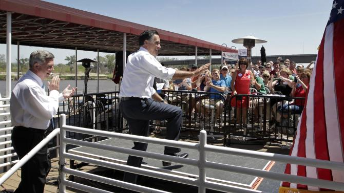 "FILE - In this May 10, 2012, file photo Republican presidential candidate, former Massachusetts Gov. Mitt Romney, greets supporters in the overflow area of a campaign stop in Omaha, Neb. Introducing Romney, Nebraska Gov. Dave Heineman, left, reminded supporters that ""the economy, jobs and health care"" will decide the presidential race. Romney thanked mothers and entrepreneurs, targeted President Barack Obama on health care and big-government spending, but stayed silent on Obama's embrace of gay marriage. (AP Photo/Jae C. Hong, File)"