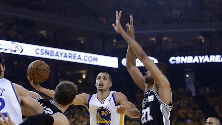 Golden State Warriors guard Stephen Curry (30) shoots around San Antonio Spurs forward Tim Duncan (21) in the first quarter of Game 6 of a Western Conference semifinal in the NBA basketball playoffs, in Oakland, Calif., Thursday, May 16, 2013. (AP Photo/Marcio Jose Sanchez)