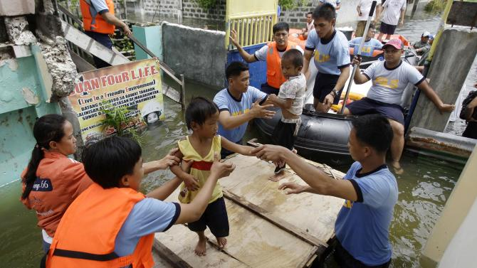 Rescuers move children to an evacuation center at Malabon city, north of Manila, Philippines on Wednesday, Aug. 1, 2012. Fierce winds and heavy rains from the slow-moving Typhoon Saola battered the country, displacing 154,000 people. (AP Photo/Aaron Favila)