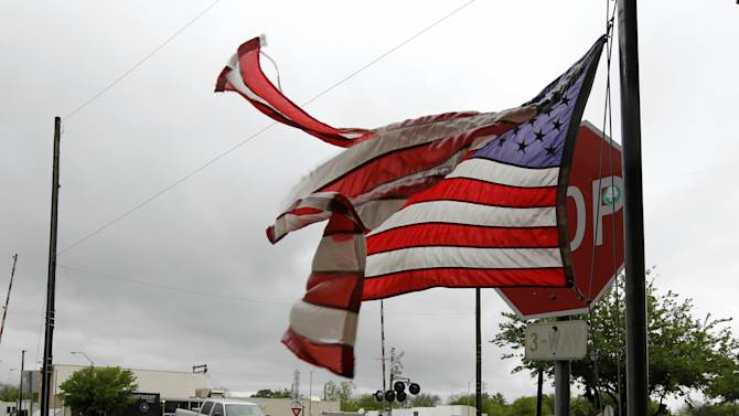 A tattered U.S. flag flies on Main Street in West, Texas on Thursday April 18, 2013 after the fertilizer plant explosion. Mangled metal and crushed vehicles are all that remains at the blast site of the fertilizer company, Thursday, April 18, 2013 in West Texas.  A massive explosion at the West Fertilizer Co. killed as many as 15 people and injured more than 160, officials said overnight.  The explosion that struck around 8 p.m. Wednesday, sent flames shooting into the night sky and rained burning embers and debris down on shocked and frightened residents. (AP Photo/The Fort Worth Star-Telegram, Ron T. Ennis)  MAGS OUT; (FORT WORTH WEEKLY, 360 WEST)