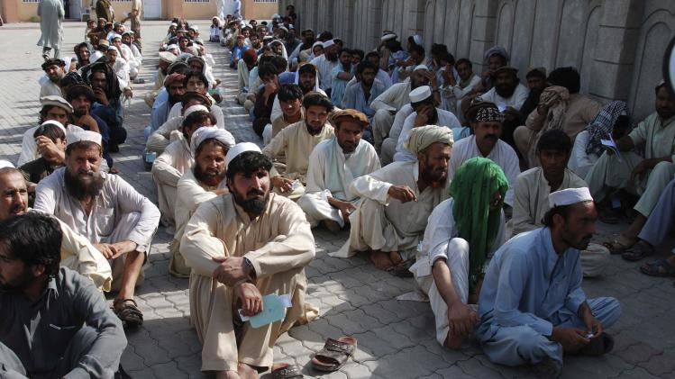 Men fleeing military offensive in North Waziristan wait to receive relief handouts in Bannu