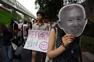 "A Thai activist holds a sign calling for reform of the lese majeste or ""royal insult"" law in Thailand's Criminal Code, while another one holds a mask representing a man imprisoned under the law during a march in Bangkok in 2011"