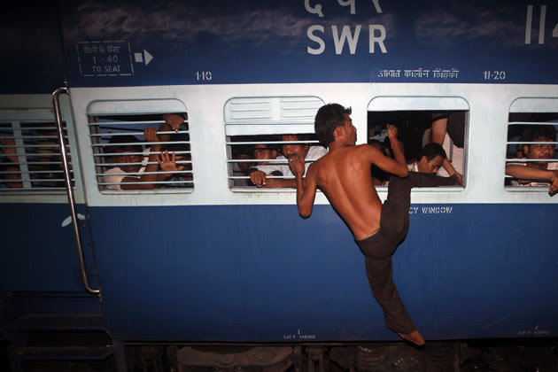 Man from India's northeastern state tries to board overcrowded train through window before it leaves for Assam state at railway station in Kolkata