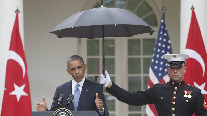 A Marine holds a umbrella as President Barack Obama speaks during his joint news conference with Turkish Prime Minister Recep Tayyip Erdogan, Thursday, May 16, 2013, in the Rose Garden of the White House in Washington. (AP Photo/Charles Dharapak)
