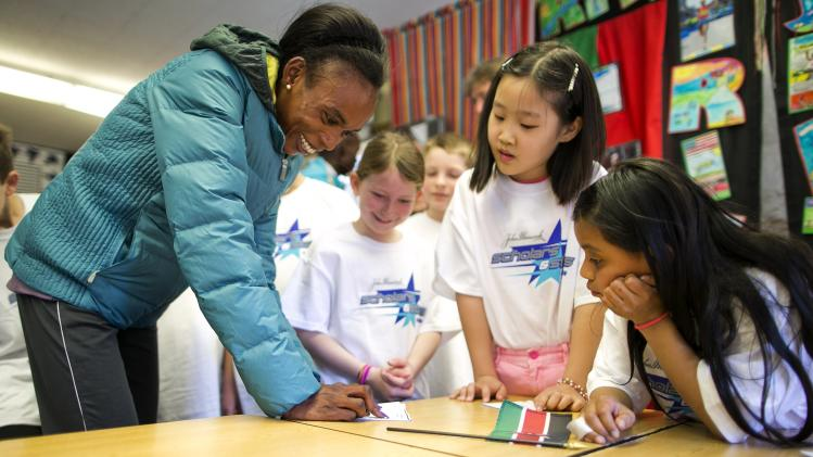 Marathoner Rita Jeptoo of Kenya teaches a Swahili lesson to second graders as elite runners from the Kenyan team meet students at Elmwood Elementary School in Hopkinton