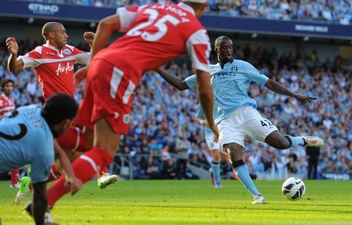 Manchester City&#39;s midfielder Yaya Toure (R) scores during their English Premier League football match against Queens Park Rangers at The Etihad stadium in Manchester. Manchester City won 3-1