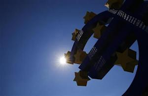Sun is seen over the euro sign landmark next to the head quarters of the European Central Bank prior to the ECB's monthly press conference in Frankfurt