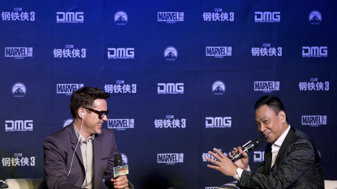 "U.S. actor Robert Downey Jr., left, shares a light moment with Chinese actor Wang Xueqi on stage during a world premiere event of his new movie ""Iron Man 3"" at a Beijing hotel Saturday, April 6, 2013. (AP Photo/Andy Wong)"