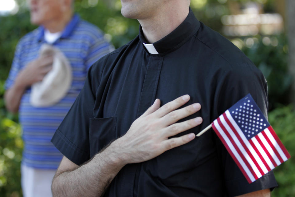 The Rev. Christopher Cooke and others cover their hearts during the playing of patriotic music during a protest against the Obama administration mandate that employers provide workers birth control coverage, at Independence Mall, Friday, June 8, 2012, in Philadelphia. The event was organized by Stand Up For Religious Freedom. (AP Photo/Matt Rourke)