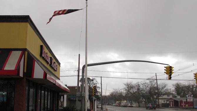 An American flag whips helplessly in the wind near a traffic light that lost power in superstorm Sandy on Tuesday, Oct. 30, 2012, in Freeport, N.Y. on Long Island. President Barack Obama declared a major disaster in New York city and Long Island. (AP Photo/Frank Eltman)