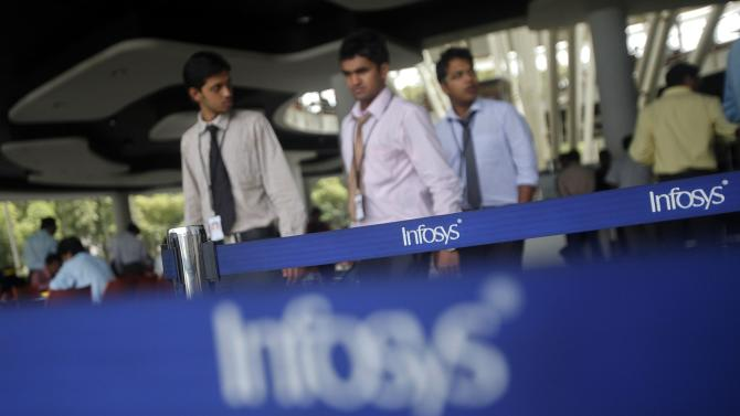 File photo shows employees of Indian software company Infosys walking past Infosys logos at their campus in the Electronic City area in Bangalore