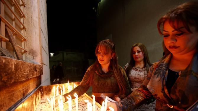 Iraqi Christians light candles during a mass on Christmas eve at Sacred Heart Catholic Church in Baghdad