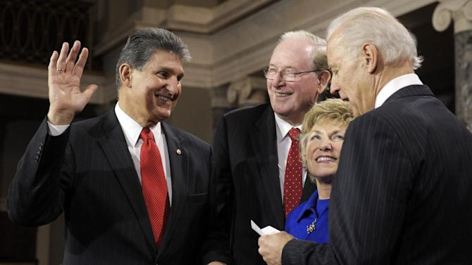 FILE - In this Jan. 3, 2013, file photo, Vice President Joe Biden administers the Senate Oath to Sen. Joe Manchin, D-W.Va., accompanied by his wife Gayle and Sen. Jay Rockefeller, D-W.Va., during a mock swearing in ceremony on Capitol Hill in Washington. Senate Democrats are approaching decision time on whether they can get Republican support for expanding background checks for firearms sales or will have to take the shakier path of pursuing the cornerstone of the gun control effort on their own. Democrats were to meet Tuesday, April 9, 2013, to discuss whether Manchin has been able to reach compromise with Republican Sen. Pat Toomey of Pennsylvania. (AP Photo/Cliff Owen, File)