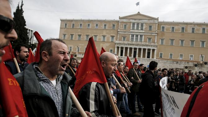 Protesters from the Communist-affiliated trade union PAME shout slogans as they join a demonstration of Greek farmers against planned pension reforms in front of the parliament building in Athens