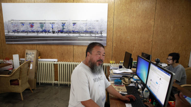 Dissident artist Ai Weiwei, left, waits at home for a verdict on his lawsuit in Beijing, China, Friday, July 20, 2012. Chinese police on Friday barred Ai from attending the verdict on a lawsuit by his company against Beijing tax authorities. (AP Photo/Ng Han Guan)