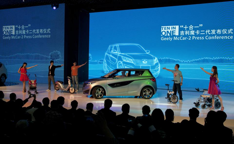Chinese dancers performs next to the new Geely McCar-2 after it was unveiled at the Beijing International Automotive Exhibition in Beijing, China on Monday, April 23, 2012. (AP Photo/Andy Wong)