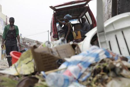 People walk past a pile of garbage along a street during rainfall, in Luanda