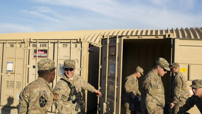 U.S. soldiers load bags into a container in preparation for leaving Afghanistan