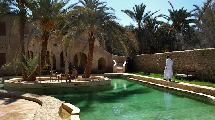 This September 2012 photo shows people by a freshwater pool at the Ghaliet Ecolodge and Spa in the Egyptian oasis of Siwa, a Berber town of some 27,000 people roughly 450 miles (about 725 kilometers) southwest of Cairo. The palm tree-lined area is known for its quiet charm, ancient ruins, abundant natural springs, a vast salt lake and rolling sand dunes in the surrounding desert. (AP Photo/Kim Gamel)