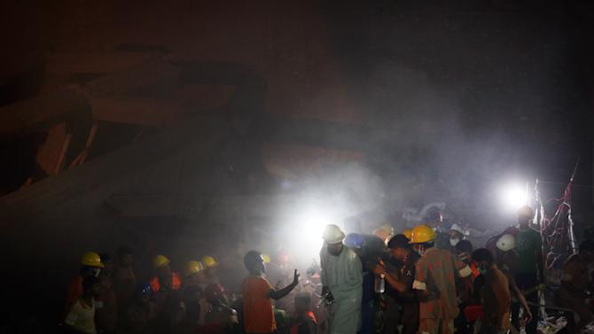 Rescue workers help to put out a fire which broke out in a garment factory building which collapsed Wednesday in Savar, near Dhaka, Bangladesh, Sunday April 28, 2013. A fire broke out late Sunday in the wreckage of the garment factory that collapsed last week in Bangladesh, with smoke pouring from the piles of shattered concrete and some of the rescue efforts forced to stop. The fire came four days after the collapse, as rescuers were trying to free a woman they found trapped in the rubble.(AP Photo/Wong Maye-E)
