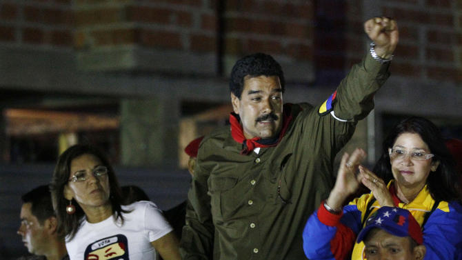 Venezuela's interim President Nicolas Maduro clenches his fist to greet supporters from the top of a vehicle as he campaigns in Caracas, Venezuela, Friday, April 5, 2013. The presidential election to replace Venezuela's late President Hugo Chavez is scheduled for April 14. (AP Photo/Ariana Cubillos)