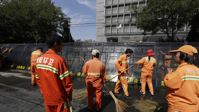 Chinese cleaners wash the barricade outside the entrance to the Japanese Embassy in Beijing, China, Wednesday, Sept. 19, 2012. People across China have engaged in days of furious protests over some East China Sea islands, claimed by Beijing and Tokyo, that Japan purchased last week from a private owner. (AP Photo/Ng Han Guan)