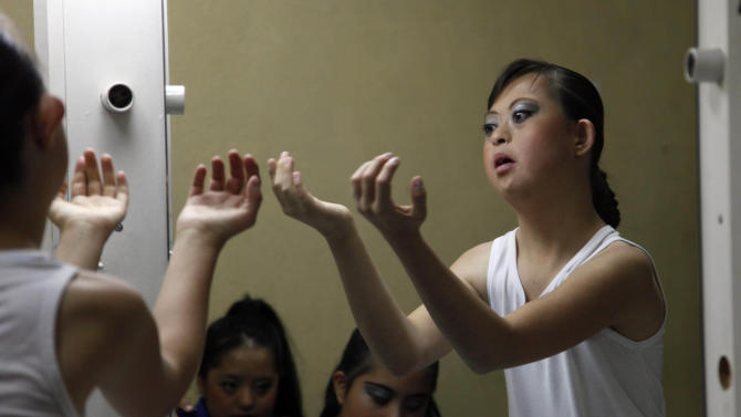 """In this Sept. 21, 2012 photo, dancer Jessica Diaz rehearses in front of a mirror ahead of her performance in """"Suenos,"""" or """"Dreams,"""" one of Ecuador's most successful musicals, at the Casa de la Cultura theater in Quito, Ecuador. The musical is based in part on the dreams of young people with disabilities and is presented by the nonprofit foundation El Triangulo. (AP Photo/Dolores Ochoa)"""