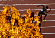 An athlete passes the Olympic flame during a men's 4 x 400-meter relay heat during the athletics in the Olympic Stadium at the 2012 Summer Olympics, London, Thursday, Aug. 9, 2012. (AP Photo/Daniel Ochoa De Olza)
