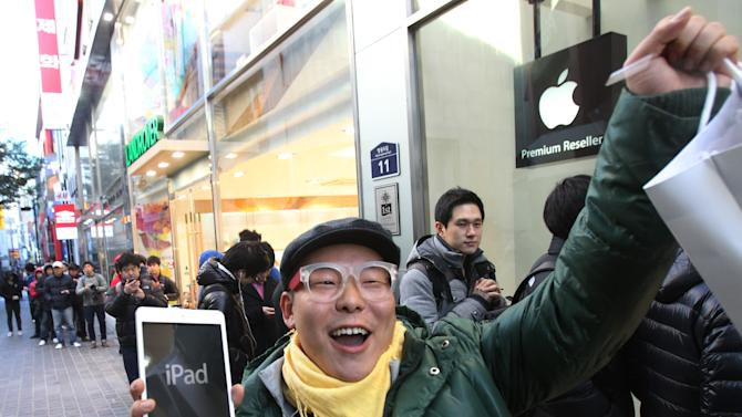 FILE -In this Friday, Nov. 2, 2012, file photo, a customer, Song Tae-min reacts after buying a new iPad Mini in Seoul, South Korea. The tablet computer is without a doubt the gift of the year. just like it was last year. But if you resisted the urge in 2011, now is the time to give in. This season's tablets are better all around. Intense competition has kept prices very low, making tablets incredible values compared to smartphones and PCs (AP Photo/Ahn Young-joon)