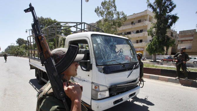 A Syrian army soldier secures the scene as he stands next to a military truck which was attacked by a roadside bomb, in Daraa city, southern Syria, on Wednesday May 9, 2012.  The explosion targeted the Syrian military truck just seconds after a team of U.N. observers passed by. An Associated Press reporter who was traveling in the U.N. convoy said three bloodied Syrian soldiers were rushed from the scene after Wednesday's blast, but the U.N. convoy was not hit.(AP Photo/Muzaffar Salman)
